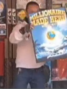 """San Jose store owner who sold winning mega million lottery ticket holds up sign that reads """"Millionairs made here"""""""