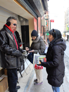 Henry Chang gives away copies of his first book, Chinatown Beat, during the Lunar New Year in New York City