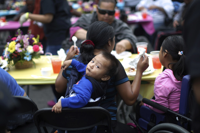 People receive a meal at a Good Friday Easter event sponsored by the Los Angeles Mission to help the homeless and near-homeless of Skid Row in Los Angeles, California, April 18, 2014. The homeless population in Los Angeles County rose 15 percent from 2011 to 2013 to nearly 53,800, according to a report from the Department of Housing and Urban Development. The largest and densest concentration live in the downtown streets of Skid Row. REUTERS/David McNew (UNITED STATES - Tags: SOCIETY) - RTR3LV89