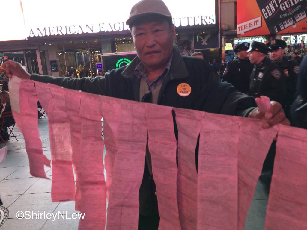 Asian street vendor puts together over 160 tickets in the form of the Tibetian prayer flag.