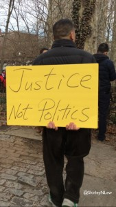 "Man holds sign, ""Justice Not Politics"""