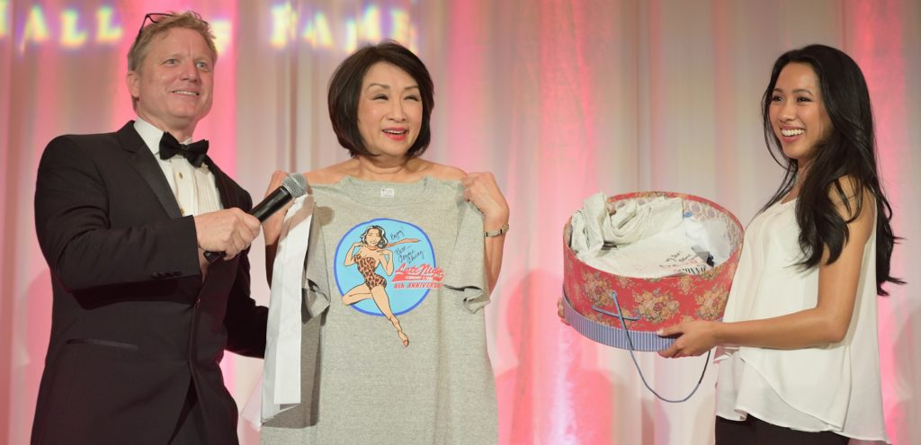 Chung, Connie holds up auction item at Asian Hall of Fame induction
